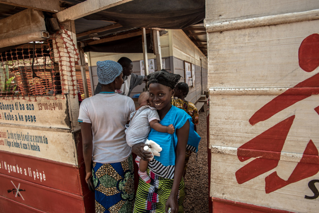 A mother leaves the MSF hospital in Bangui, Central African Republic, where obstetrician Rennie Urquhart has been working. She smiles broadly as she holds her baby.