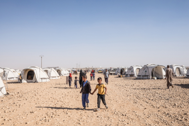 Kids walk on a sandy track among the white tents at Ain Issa camp, Syria