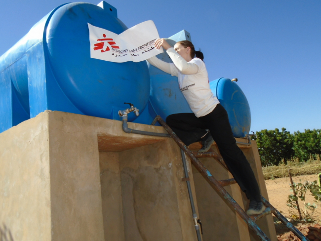 Veronica climbs a ladder to affix the MSF logo to a water tank