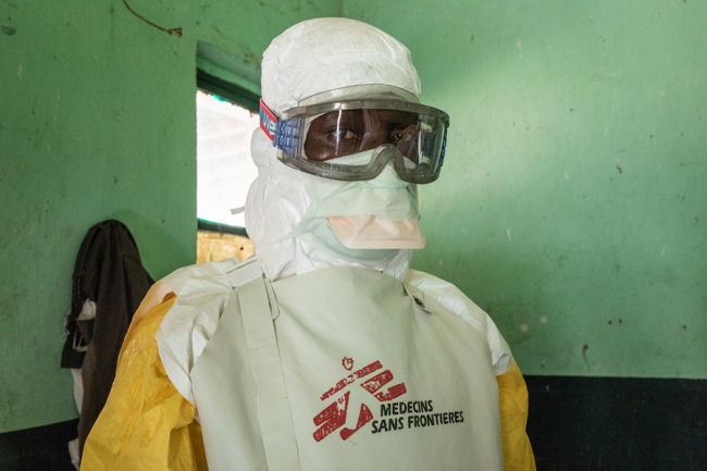An MSF team member get dressed into a full protective suit. Photo: Louise Annaud/MSF