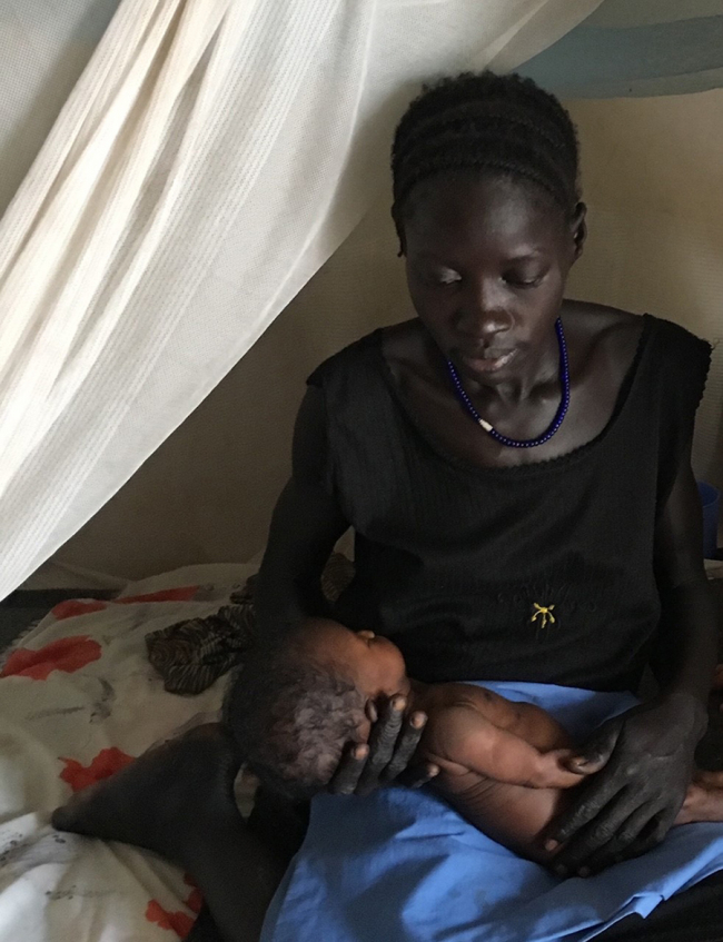A young woman holds a newborn baby in her lap at the MSF hospital in Lankien, South Sudan