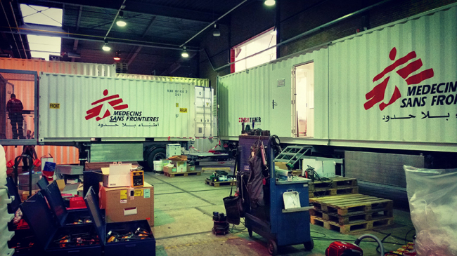 Two trailers in a warehouse show large MSF logos on the side
