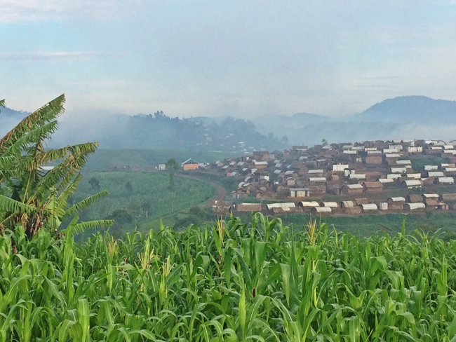 Mweso displaced person's camp sits on the crest of a hill, surrounded by vibrant green fields and the early morning mist