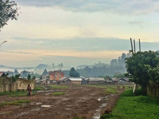The muddy road that leads into Mweso town in DRC, with the mist-shrouded mountains in the distance