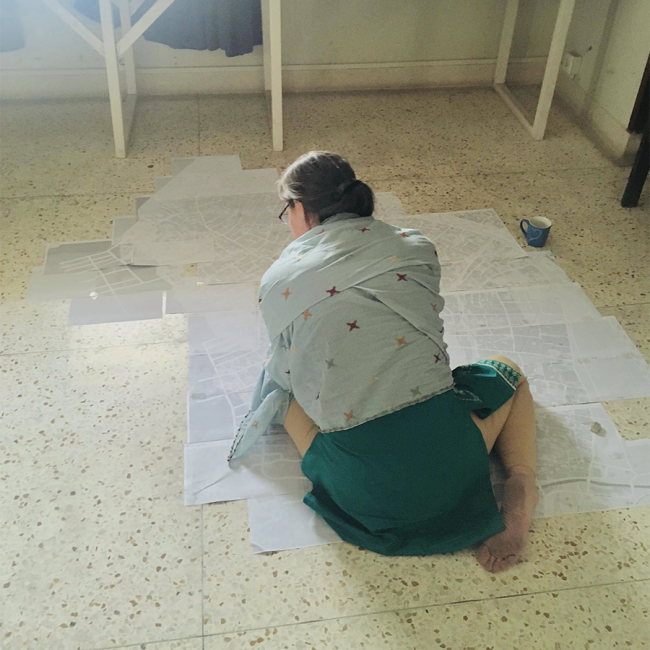 Nance sits on the floor, in front of a patchwork of print-outs