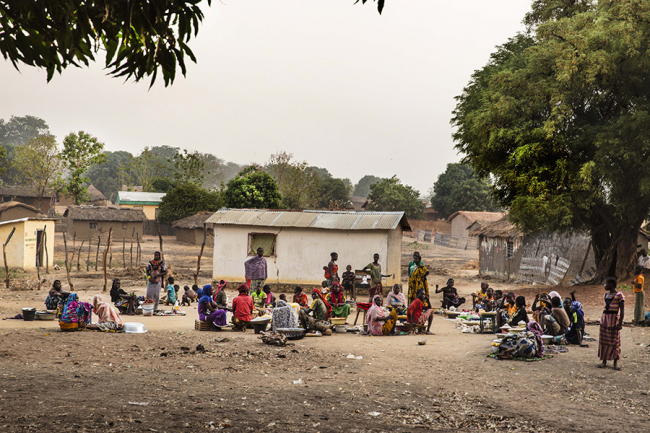 Image shows a small village with around 30 people sitting together at a small market