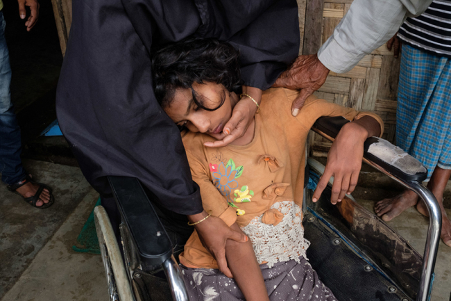 Image shows a Rohingya refugee girl in a wheelchair at one of MSF / Doctors Without Borders' clinics in Bangladesh