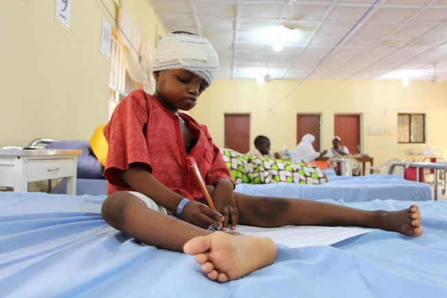A child recovers from reconstructive surgery for injuries caused by noma