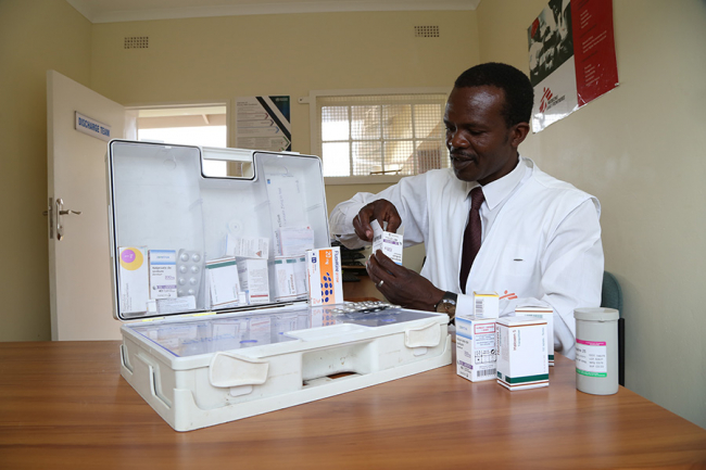 Image shows Norman sitting at a table with a large case of different medications