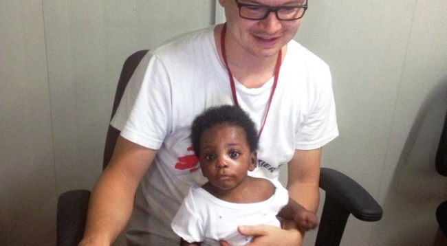 Photo of MSF staff member with orphaned child