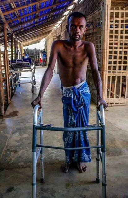 Image shows a young man using a Zimmer frame
