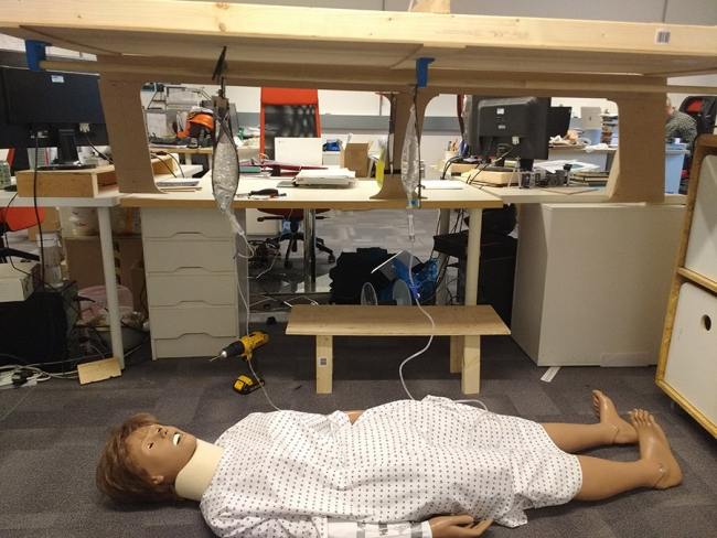 Photo of the wooden model of the land cruiser, and a dummy dressed as a patient lying on the floor