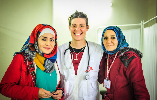 Image shows three smiling nurses, one of whom wears an MSF jacket and a stethoscope