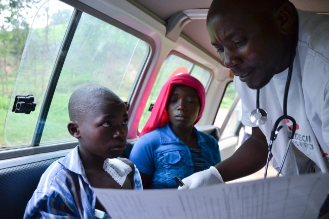 Simweray's medical history is taken by an MSF nurse in the back of the ambulance.