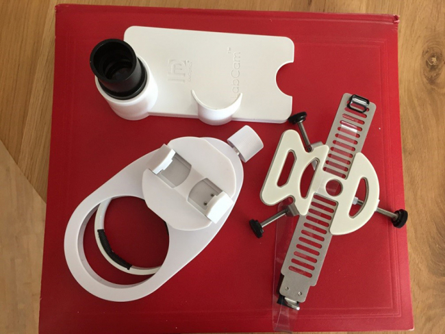 Image shows three white plastic devices, which look like a car cup holder, a mobile phone case , and a strange vice type gadget