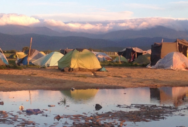 Tents with the mountains behind wreathed in cloud