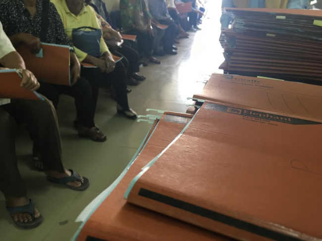 A photo shows the big pile of medical files and the patients waiting for appointments