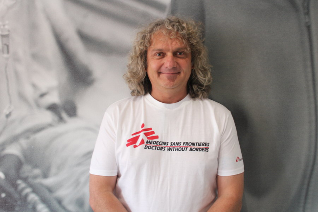 Image shows Eben, a man in his forties or fifties, with shoulder length curly blond or silver hair, wearing an MSF t-shirt