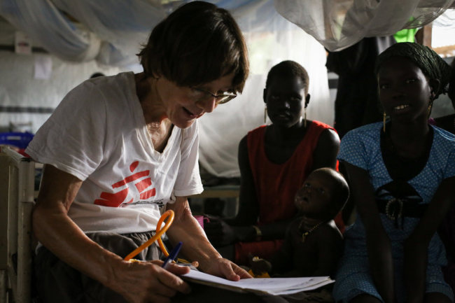 Image shows Ros looking at a chart. Two South Sudanese women sit nearby, one with a small child who has his eyes crossed