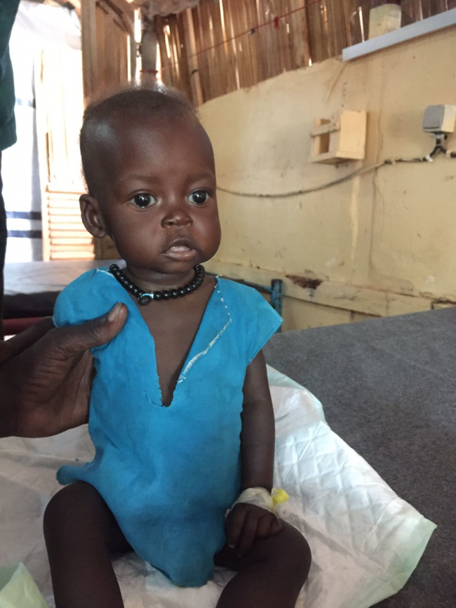 A toddler sits on a bed in the MSF hospital in Yida Camp, South Sudan. She wears a blue dress and black beads