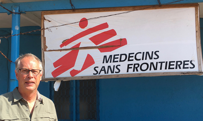 Image shows Russ, a man in his 40s or 50s, wearing glasses, standing in front of an MSF sign
