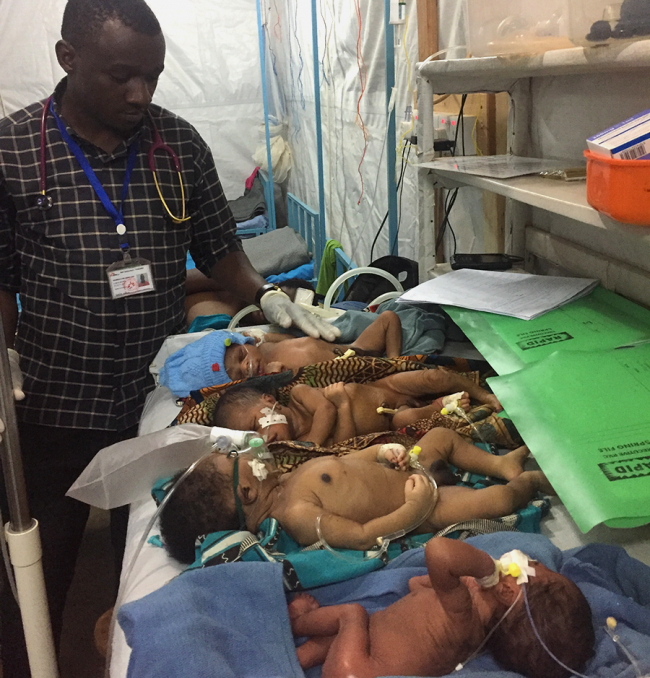 The clinical officer checks on four infants in the newborn ward