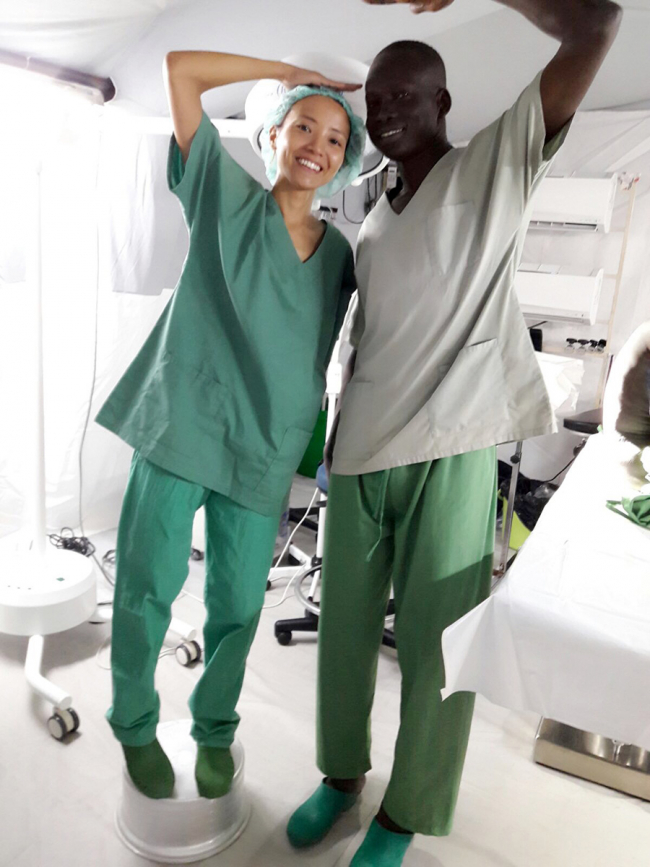 Image shows a young woman in green scrubs, standing on a cooking pot next to a man who is still about 10 inches (25cm) taller than her
