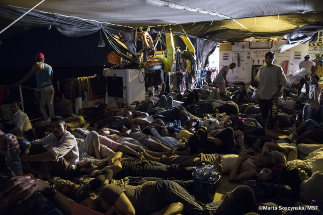 People sleep on the deck of the ship