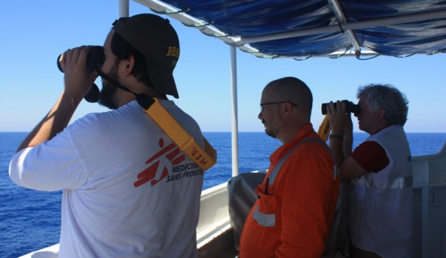The team use binoculars to search for boats in distress