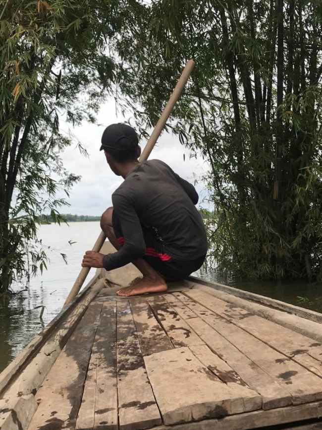 A man crouches at the prow of a wooden boat, propelling it forward with a wooden pole.