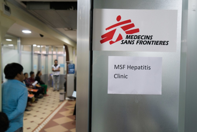 Photo shows the door of the MSF Hepatitis Clinic. The MSF logo is emblazoned on the glass door.