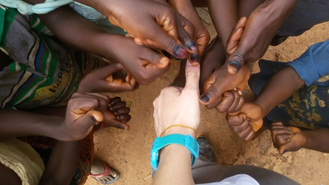 The children proudly display their marked fingers to prove that they have been vaccinated ...