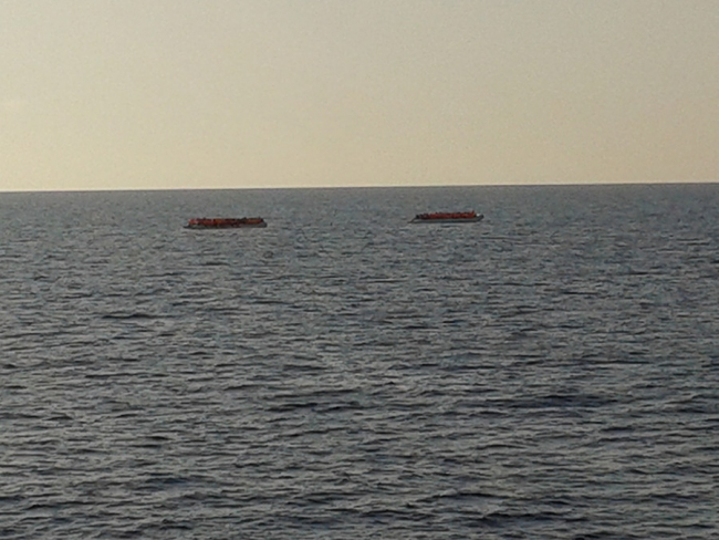 Two rubber dinghies sit on the horizon of the sea