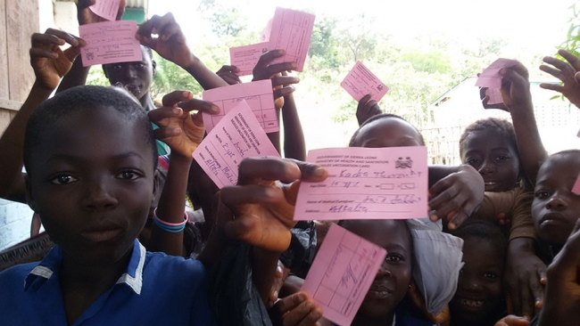 The children proudly display their pink vaccination cards...