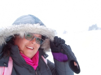 Image shows Annke in the snow in Norway, wearing a warm hood