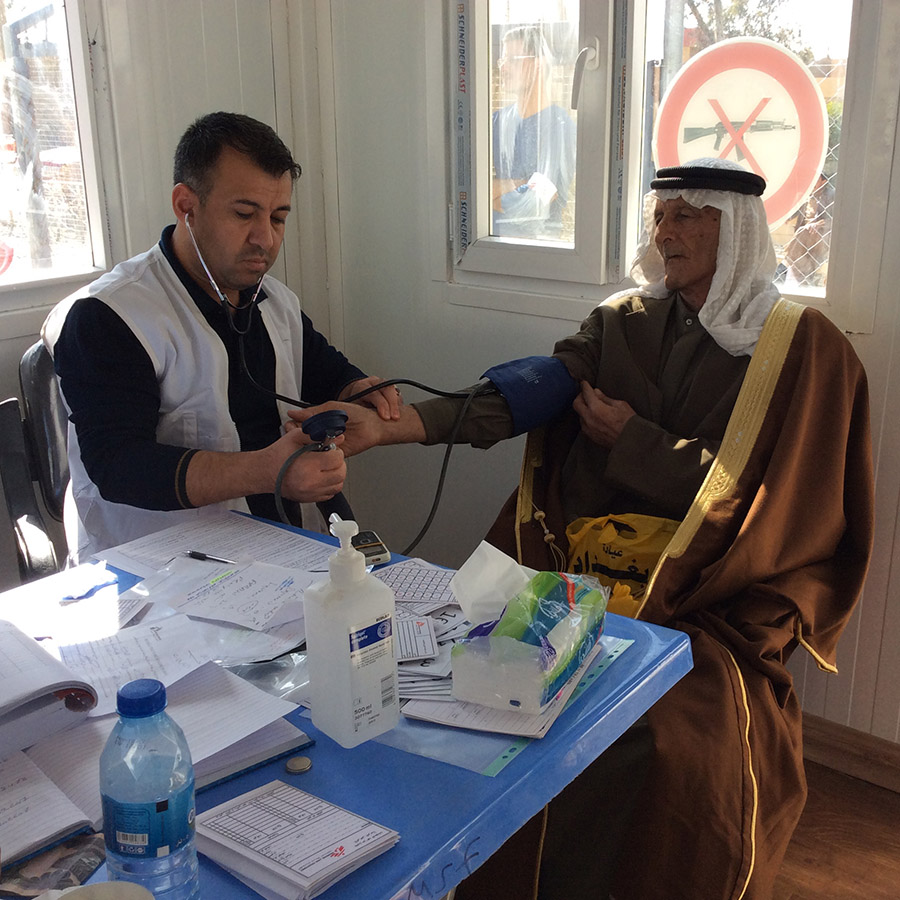 A patient's blood pressure is checked at the MSF clinic. The 'No Weapons' symbol can be seen displayed in the window