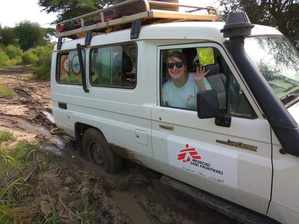 Lisa smiles from the window of a white land cruiser car as the wheels spin in the mud
