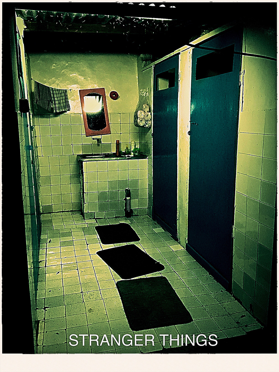 Image shows scary bathroom with green tint and the words 'Stranger Things' at the bottom of the photo