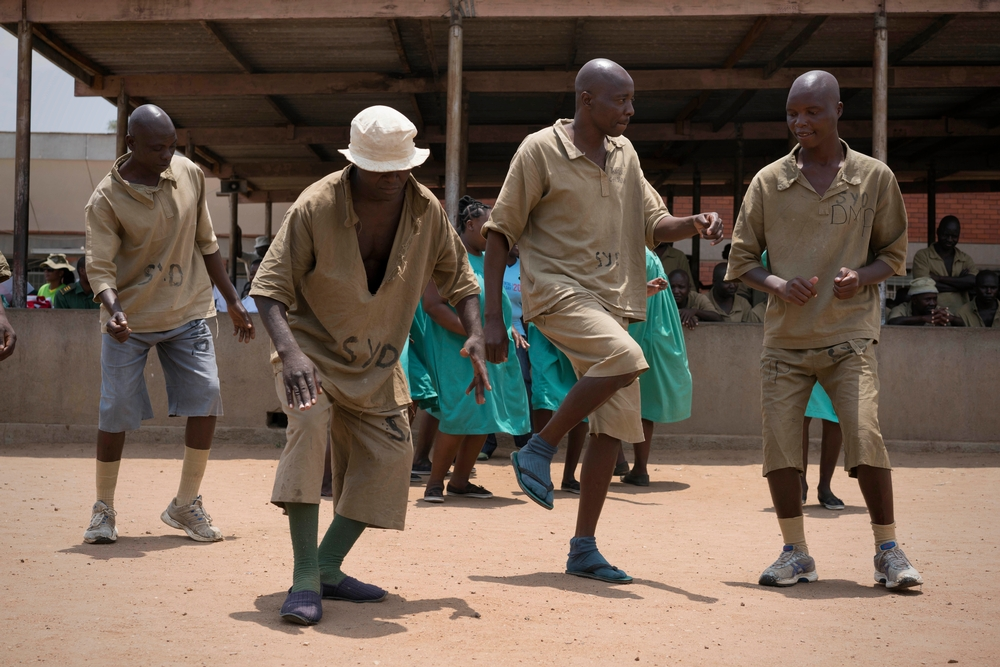 An image shows mental health patients from Chikrubi Prison dancing to commemorate World Mental Health day. Four smiling men dance in the foreground with a group of women dancing behind them. There is a flurry of bent legs and arms as they dance. A large c