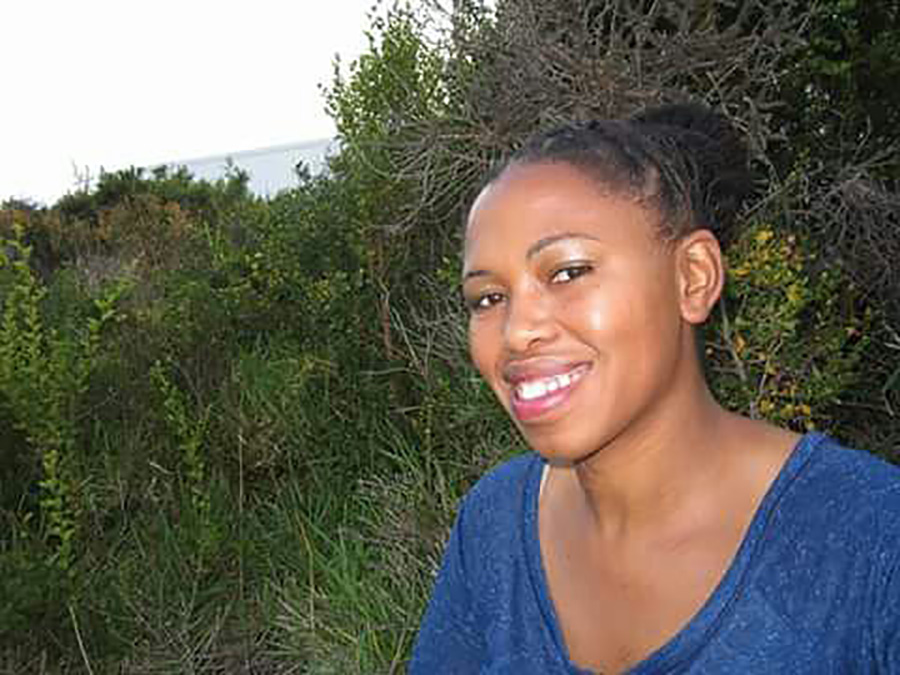 Portrait of Nandi, who wears a blue top and smiles broadly
