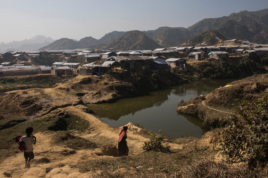 Image shows the Rohingya refugee camp in Bangladesh, which shows temporary structures with hills in the background