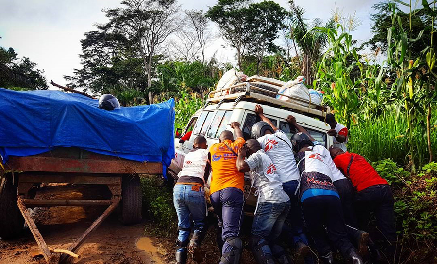 MSF landcruiser being pushed up a muddy road in DRC