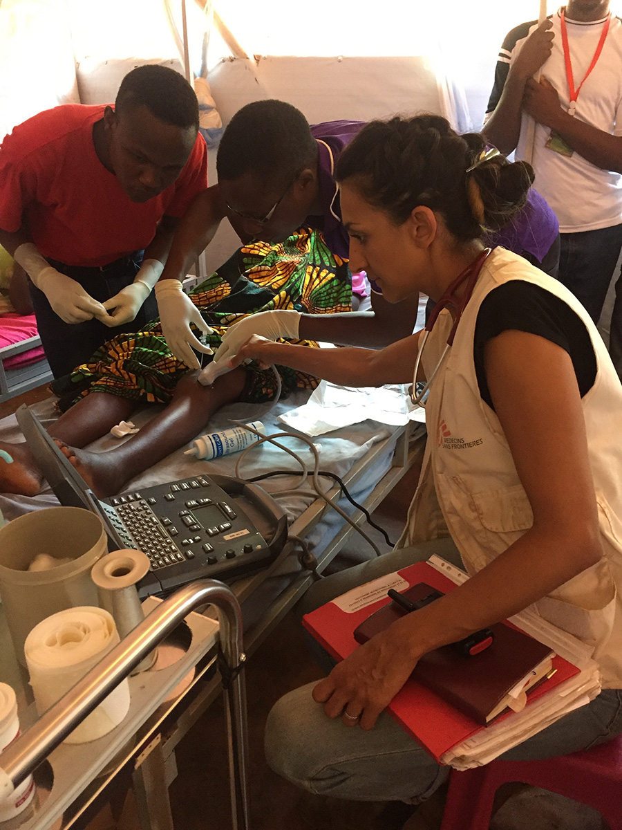 Saschveen and the team use ultrasound to examine a child's leg in the Nduta Refugee Camp, Tanzania