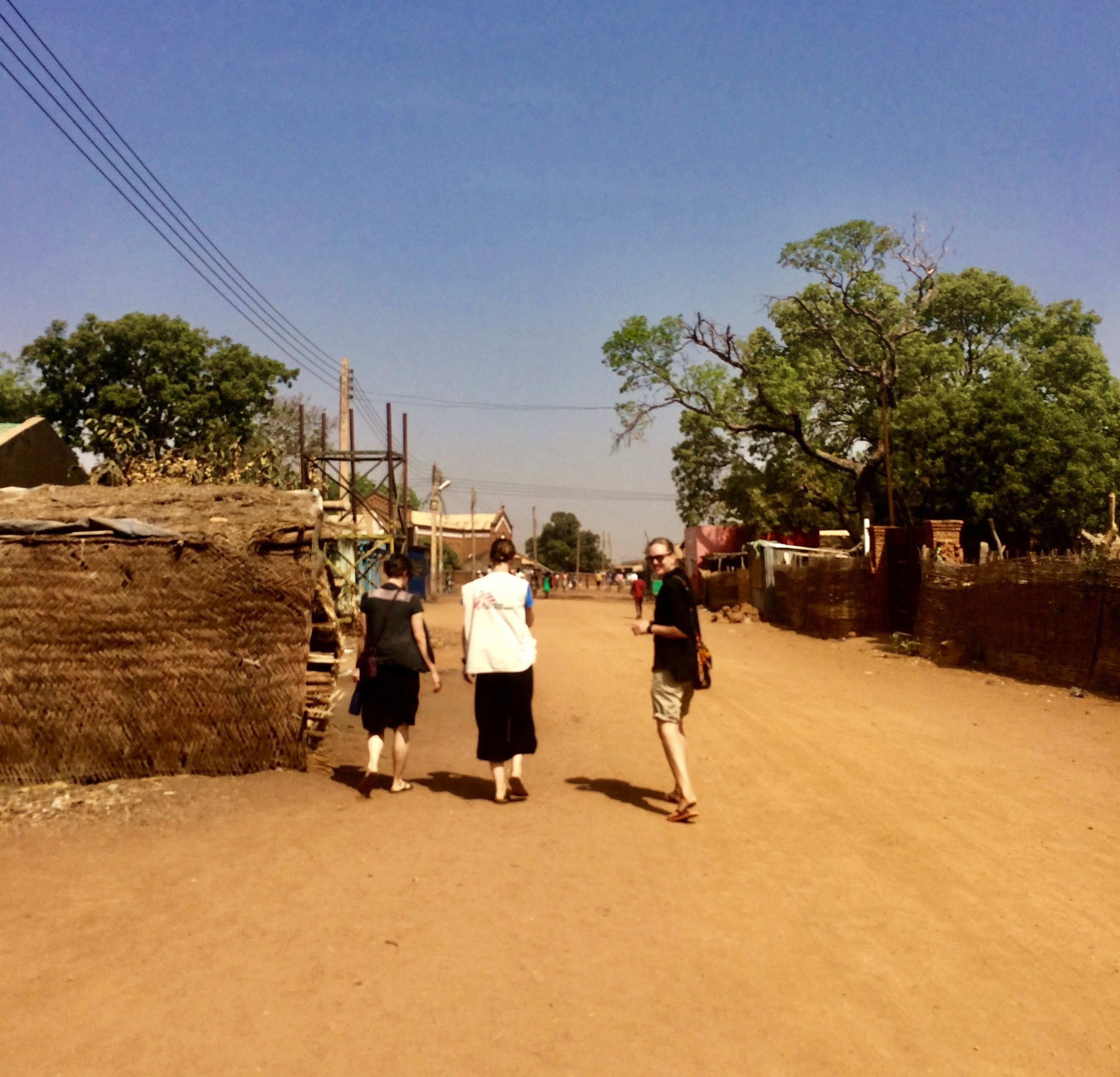 Three people walking in Aweil town