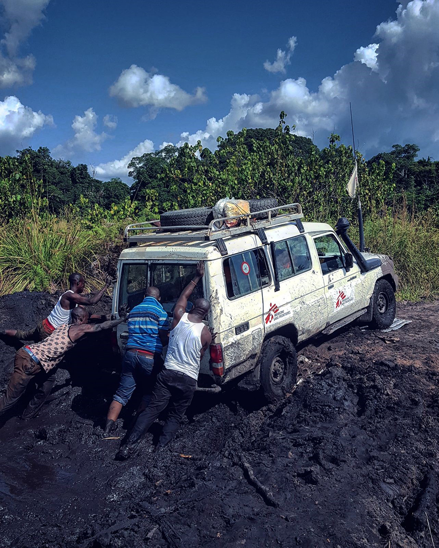 MSF landcruiser being pushed out of mud in DRC