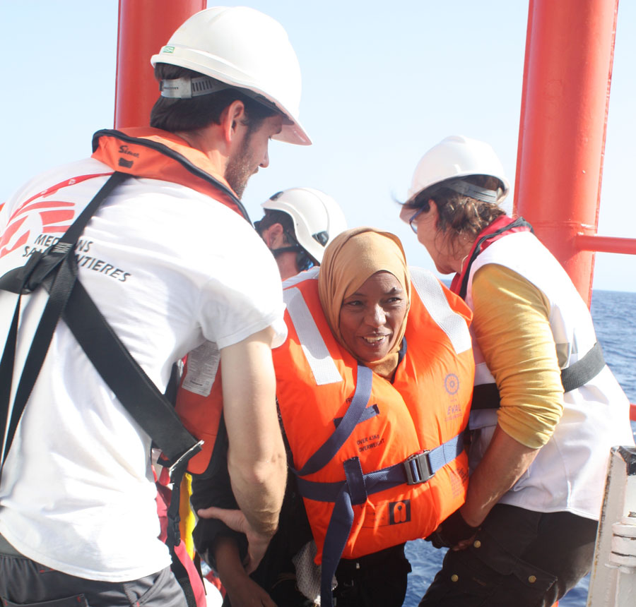 A woman is helped aboard the ship by the MSF team