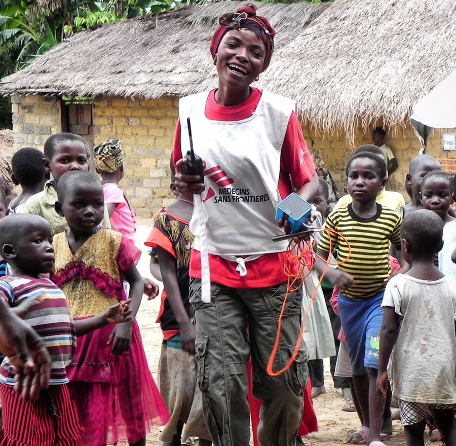 MSF health promoter Sophie singing and dancing at HAT screening in DRC