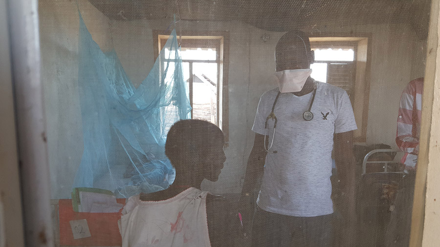 Doctor Tor consults with a TB patient. He wears a protective mask and a stethoscope.