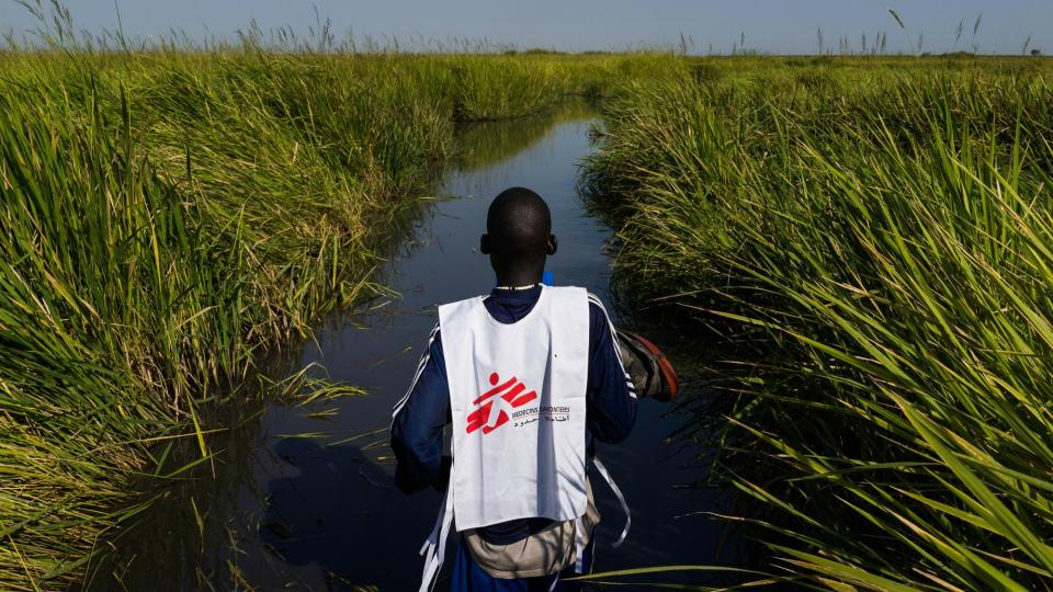 A member of MSF staff crosses a swamp in South Sudan