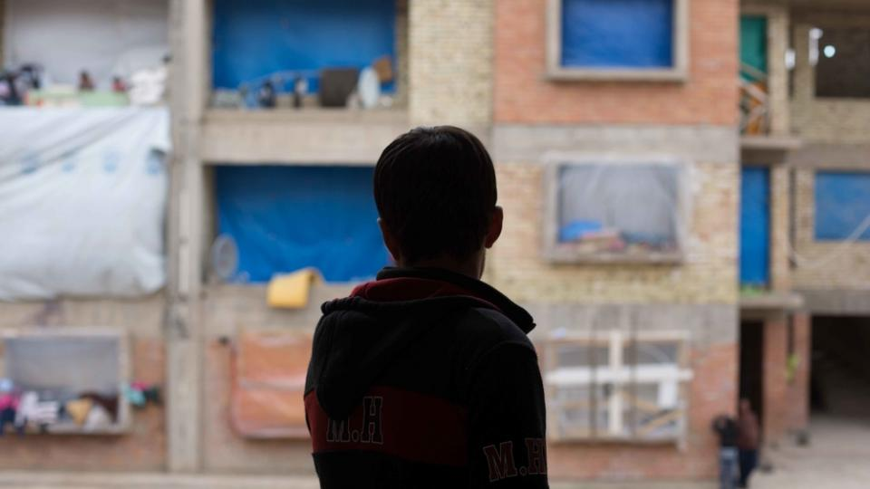 A boy is silhouetted in a window in Kirkuk, Iraq